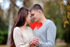 Loving couple with red heart in the autumn park. love concept Stock Photos