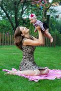 Child and parenthood concept - happy mother with little baby sitting on blank Stock Photos