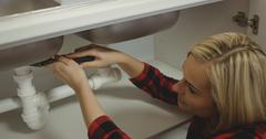 Beautiful woman repairing a tap Stock Photos
