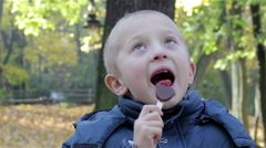 Licking chocolate candy eyes look to the top Stock Footage
