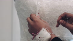 Young entrepreneur pinning wedding dress on Mannequin - stock footage
