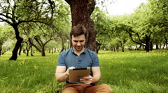 Handsome hipster man using his tablet pc on a sunny day with copy space Stock Footage