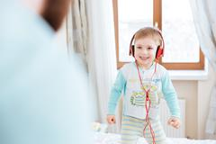 Little boy in headphones listening to music standing on bed - stock photo