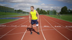 4K Portrait of disabled athlete with prosthetic leg standing at running track - stock footage
