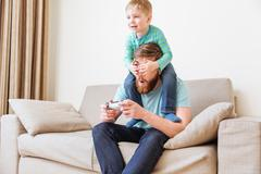 Little boy covering father eyes while he playing computer games - stock photo