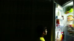 Child eating a snack in front of the refrigerator in the middle of the night Stock Footage