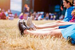 Legs of teenagers, music festival, in front of stage - stock photo