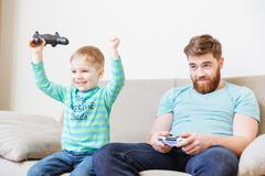 Little son playing computer games with father and winning Kuvituskuvat