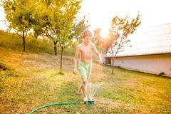 Boy at the sprinkler having fun, summer garden Stock Photos