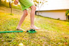 Legs of a boy in garden at the sprinkler - stock photo