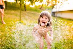 Little girl at the sprinkler having fun, summer garden Stock Photos