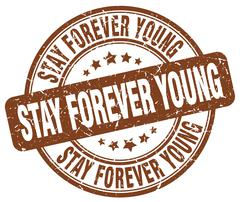 stay forever young brown grunge round vintage rubber stamp - stock illustration
