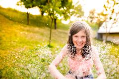 Girl in bikini sitting at the sprinkler, summer garden - stock photo