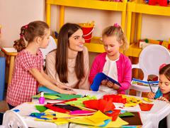 Kids holding colored paper on table in kindergarten . Stock Photos