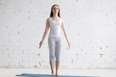 Attractive fit young woman doing Mountain pose in white loft Stock Photos