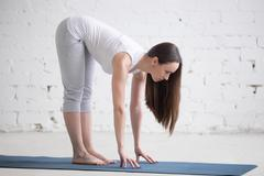 Attractive fit young woman doing Ardha Uttanasana pose in white loft - stock photo