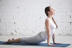 Attractive young woman doing upward facing dog pose in white loft Stock Photos