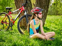 Bikes cycling girl wearing helmet sitting under tree. - stock photo