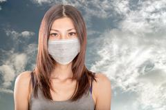 Asian woman wearing surgical mask - stock photo