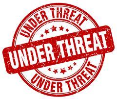 under threat red grunge round vintage rubber stamp - stock illustration