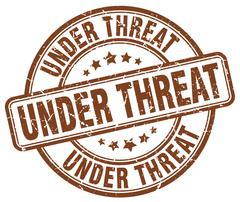 under threat brown grunge round vintage rubber stamp - stock illustration