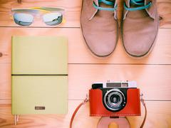 Top view set with old camera, boots, sunglasses Stock Photos