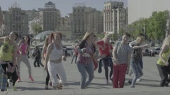 People do dance aerobics in the town square Stock Footage