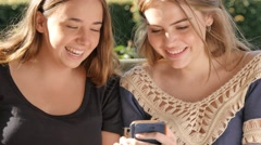 Two bff girl friends sitting on a bench looking a mobile smart phone laughing Stock Footage