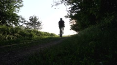 Man riding a bike on a dirt road at sunset Stock Footage