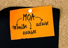 Business Acronym MOA as Monitor, Oversee, Advise written on orange paper note - stock photo