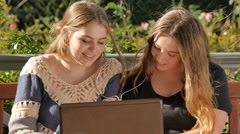 Teenage girls using laptop to chat with friends social media listening to music Arkistovideo