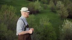 Brewer standing against a background of green hills enjoying dark beer. Stock Footage