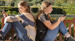 Two bored teenage girl friends texting on social media Internet technology Arkistovideo