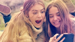 Two young woman pulling funny expression faces at mobile phone camera Stock Footage