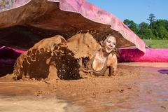Woman Splashes Crawling Through Muddy Water At Mud Run Event - stock photo