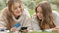 Young teenage friends online retail shopping purchasing item with credit card Stock Footage