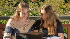 Happy young teenage girl students using laptop to study while listening to music Stock Footage