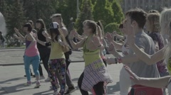 A group of people are dancing in the town square Stock Footage