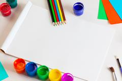 Album pages and paints, pencils, brush on a white wooden background. - stock photo