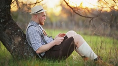 Stylish young man in the park with tablet in hands. Stock Footage