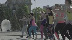 A group of people are dancing in the town square (aerobics) - stock footage