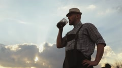 Man tasting beer on the background of the setting sun. - stock footage