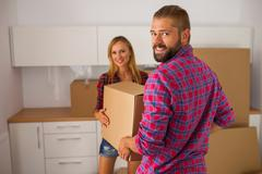 Young couple just move to their new apartment. They are unpacking stuff. Stock Photos