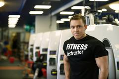 Fitness guy posing on backdrop of sports equipment - stock photo