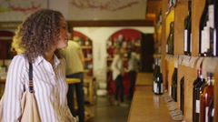 4K Attractive woman choosing which wine to buy in specialist wine store Stock Footage
