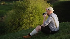 Bavarian sitting on a hill near the cliff. - stock footage