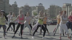A group of people doing dance aerobics in the city centre - stock footage