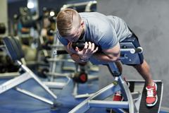 young man flexing back muscles on bench in gym - stock photo