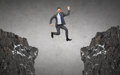 Happy smiling businessman jumping between rocks Stock Photos