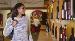 4K Attractive woman choosing which wine to buy in specialist wine store - stock footage